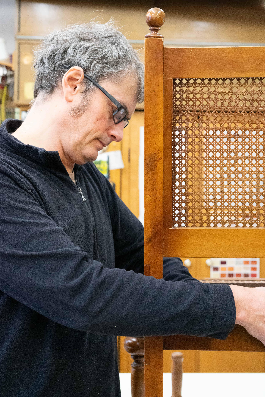 Restaurator Helmut Stöhr bei der Bearbeitung eines massiven Holzmöbelstückes