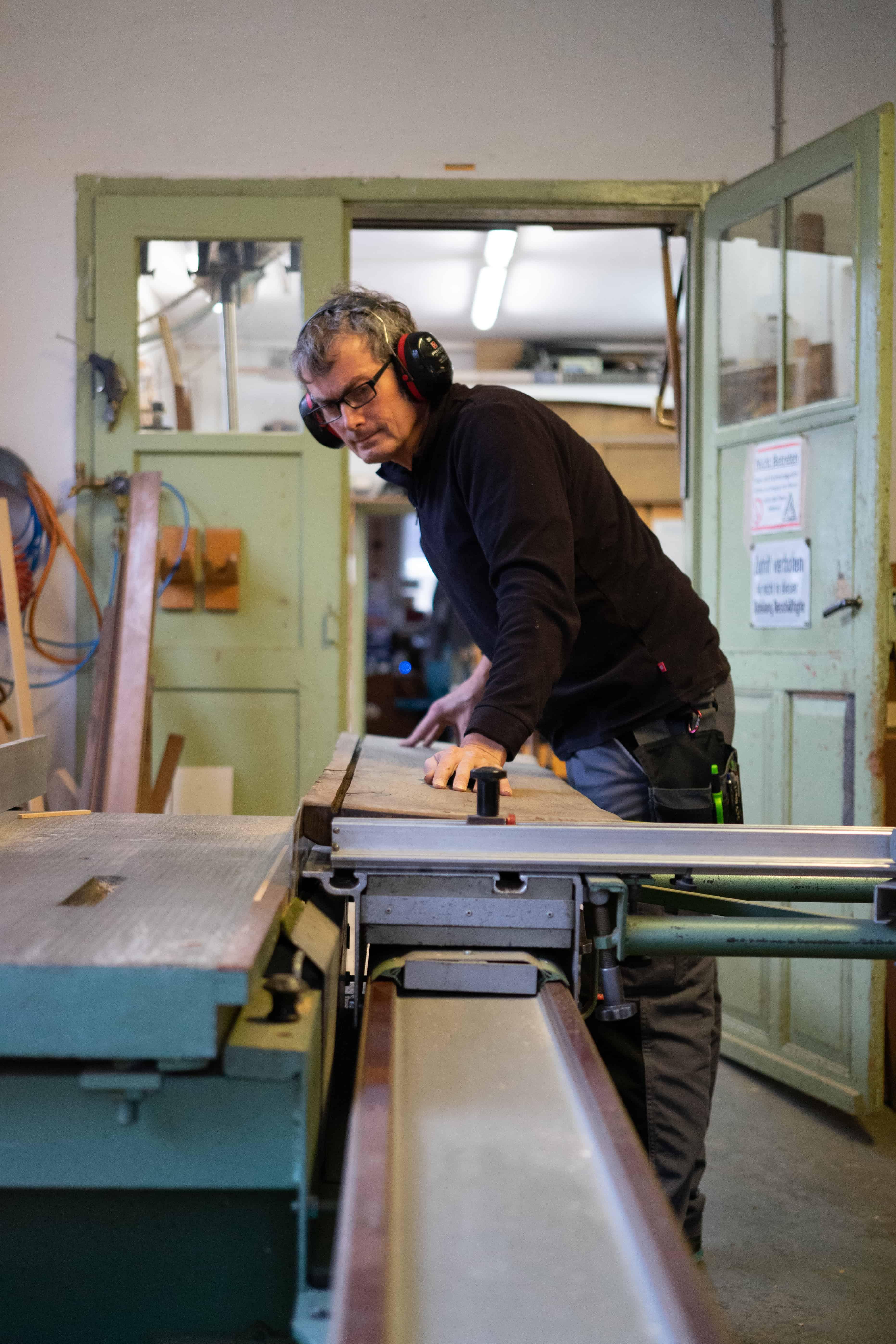 Helmut Stöhr sägt ein Holzstück für die Restaurierung eines Möbelstücks zusammen